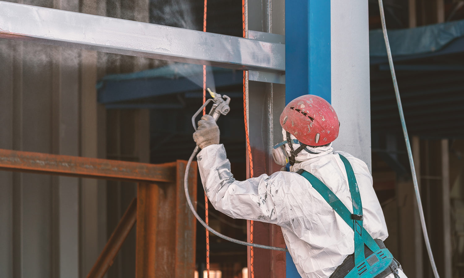Worker paints a metal frame at construction site